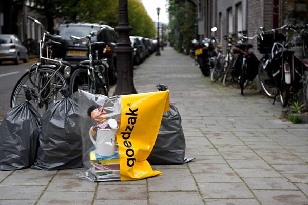 Наполовину прозрачные пакеты Goedzak, наполненные книгами, игрушками, одеждой и прочим, следует оставлять прямо около мусорных баков